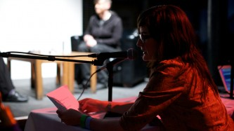 In shadow in the foreground a woman with long hair and glasses reads into a mic