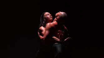 Two figures embrace, lit from above with a spotlight in dark room