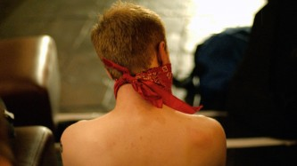 A view of Kylie Minoise's bare back with a red bandand tied around their head