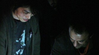 Two men concentrate in the dark lit from below by a computer screen