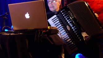 Pauline Oliveros holding an accordion while reading information from a laptop