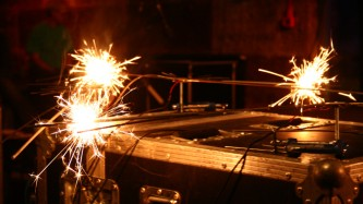 Sparklers mounted on stands with microphones being lit with a gas burner