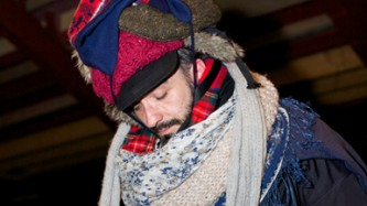 A mans face looked down peeking out from having being covered in hats and scarfs