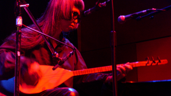 Keiji Haino playing a saz onstage in CCA Glasgow 05