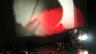 Large white and red forms projected near a man operating another projector