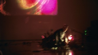 Projection of a pink and gold form above a man operating another projector