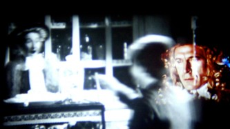 Layers of projection on a screen, a man's face with wig to the right