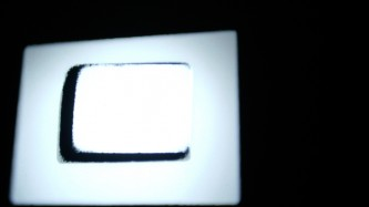 Two rectangular forms of white light against black on a screen