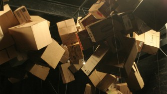 Cardboard boxes suspended in bunches from cords