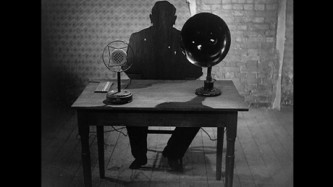 A silhouette of a man sits at a small desk with a old microphone set upon it.