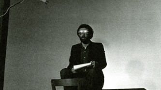 Lutz Becker reads a text, seated cross legged on a platform, against a blank wal