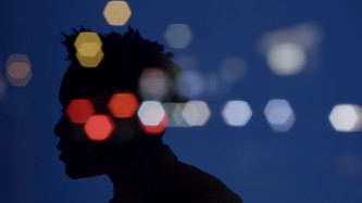 Silhouette of a person in front of a blue background overlaid with blurry light