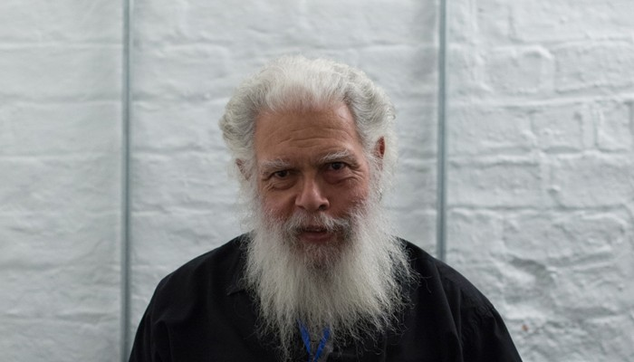 Samuel R Delany pictured backstage against a white wall, bearded