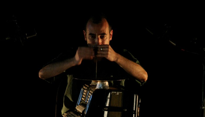 Alfredo concentratedly holding a small stick against an accordion
