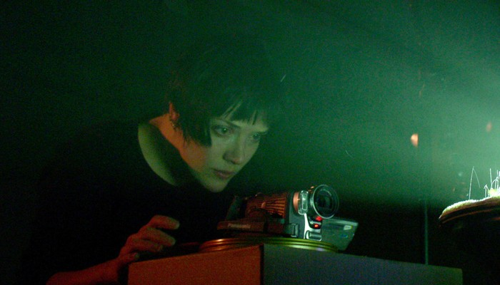 Emma Hart lit from the glare of a projector as she adjusts a camera