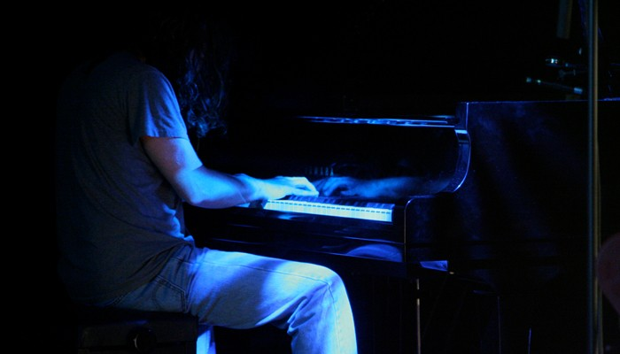 John Blum seated at a piano in blue light at MLFC 07