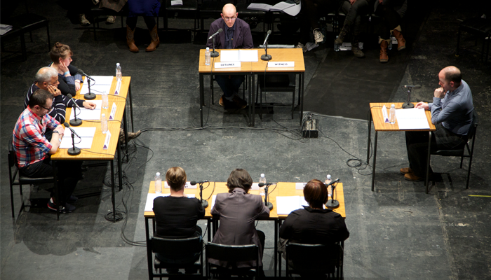 Groups of people at tables with microphones and papers