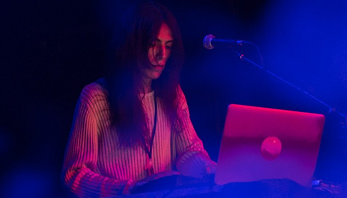 Elysia Crampton with long hair is lit by red and blue lights whilst on a laptop