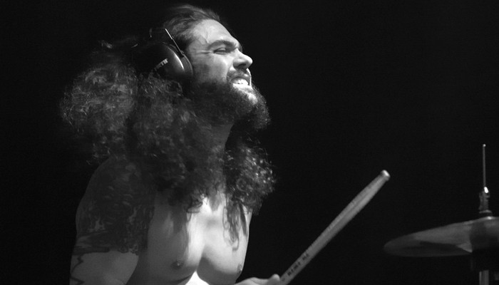 Joe Heffernan with long curly hair throws his head back as he plays the drums