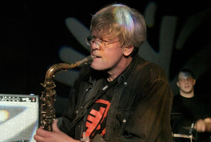 Don Dietrich with shaggy grey hair puts his saxophone to his mouth