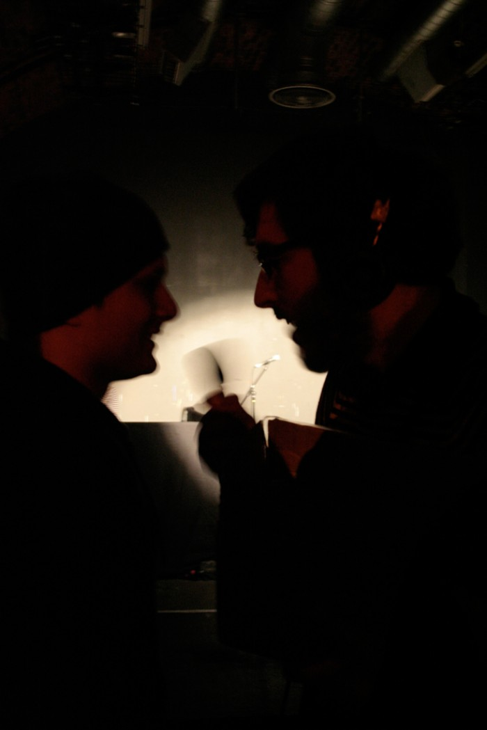 Two profiled faces in silhoutte talk, a blurred hand mic between them