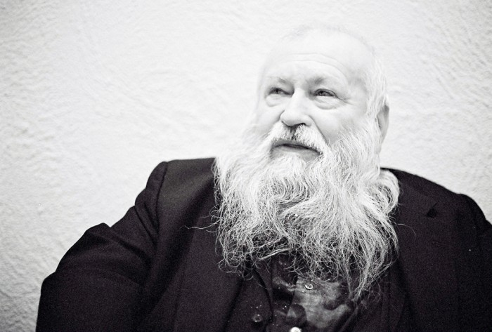 A bearded Hermann Nitsch sits back in a chair looking sideways