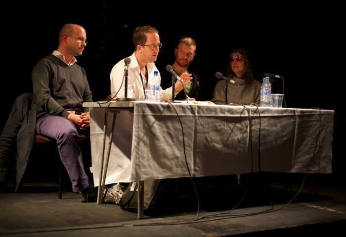 Robin MacKay sits on a panel of 4 people. He leans forward to speak into a mic