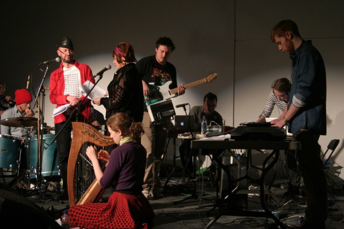 A band on stage including a harpist, a reader in a red shirt and electronics