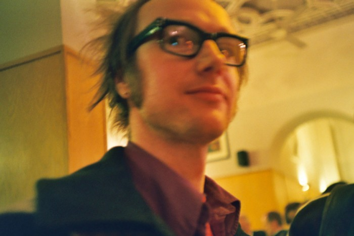 a man with dark rimmed specs and sideburns smiles at the camera