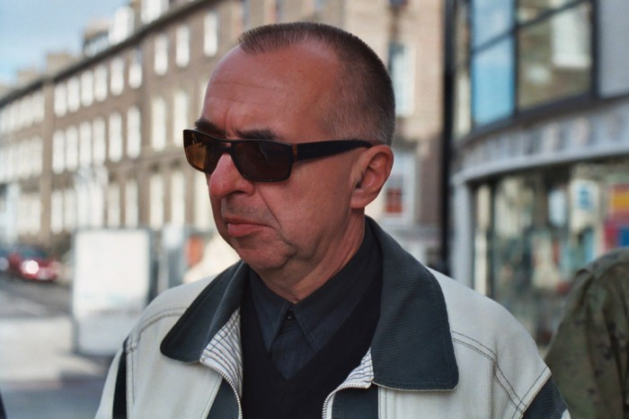 A man in sunglasses standing in front of a sunny row of tenements