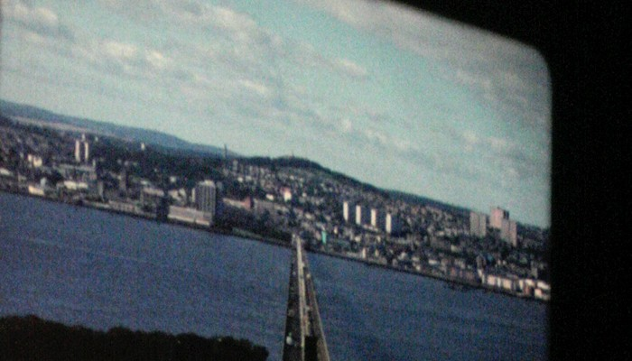 A shot of 16mm projection of the Tay Bridge straddling a sapphire blue river