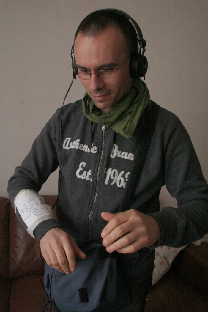 Man with headphones and sound gear looks at a score taped to his wrist