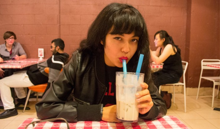 Jackie Wang drinking through a straw in a cafe