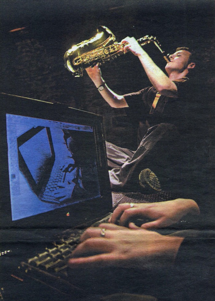 A man plays a saxophone while hands play a laptop keyboard