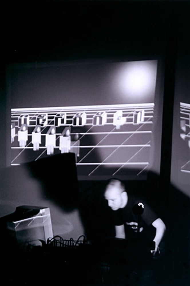 A B and w image of a man looking at a computer as digital graphics are projected