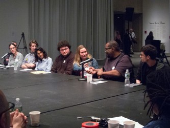 Fred Moten shakes hands with a participant as they sit with others at a table
