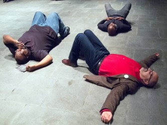 Three participants, one in red, one in browm, lie, arms wide on a stone floor