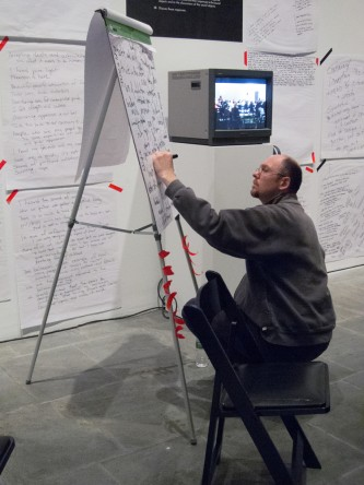 A notetaker kneels in front of a flip chart stand and writes