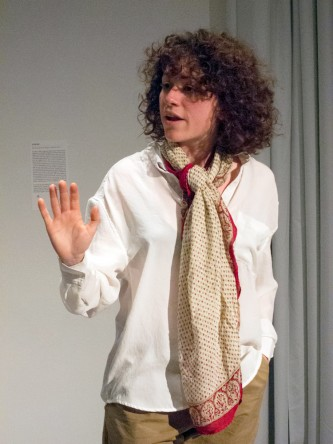A cast member dressed in a loose shirt and scarf addresses the crowd on a box