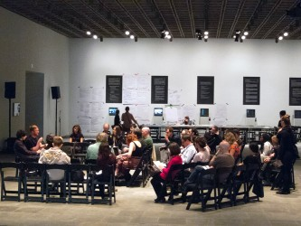 An audience sit around as Barry Esson and Jay Sanders talk in a gallery
