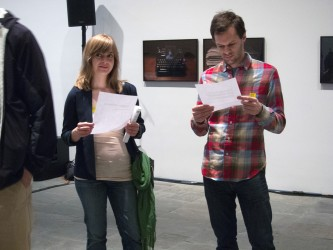 A man in a checked shirt looks down at a piece of paper, as a woman looks around