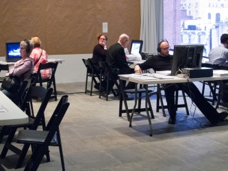 Several folks sit as table reading research and watching videos on tv screens