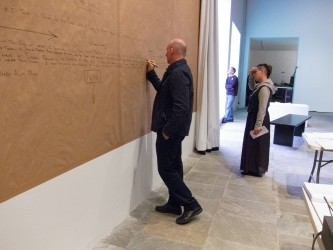 Brandon La Belle writes on walls covered with brown paper as someone looks on