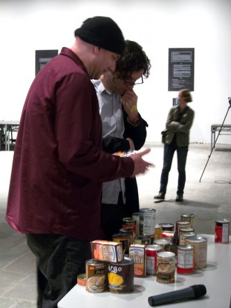 Chris Delaurenti gifts a can of food to an audience member, other cans are seen