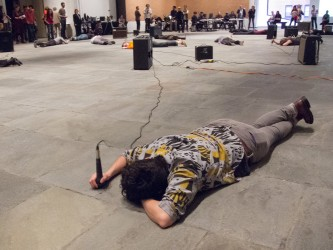 Dawn Kasper lies on the gallery floor face down and hits the floor with a mic