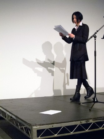 Vanessa Place walking across the stage as she reads poetry from papers