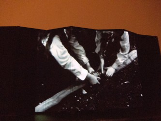 A film image of hands grabbing a stick projected onto an articulated screen