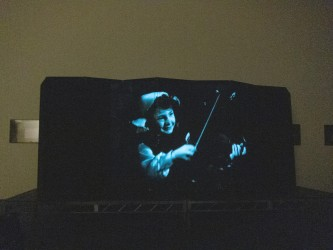 A film image of a girl playing a violin projected onto an articulated screen