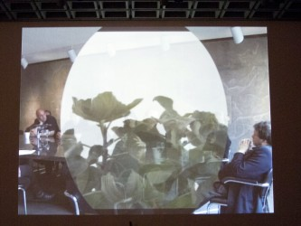 A screen showing people sat round a board table with a vinette of plants