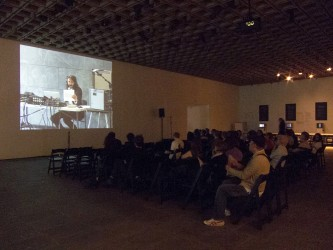 An audience sit in rows in a dark gallery watch a screen showing Rene Gabri
